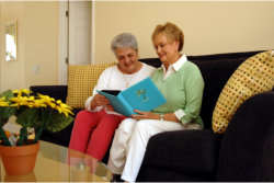 two elderly woman reading a book