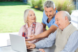 an elderly couple with a caregiver lookig at the laptop